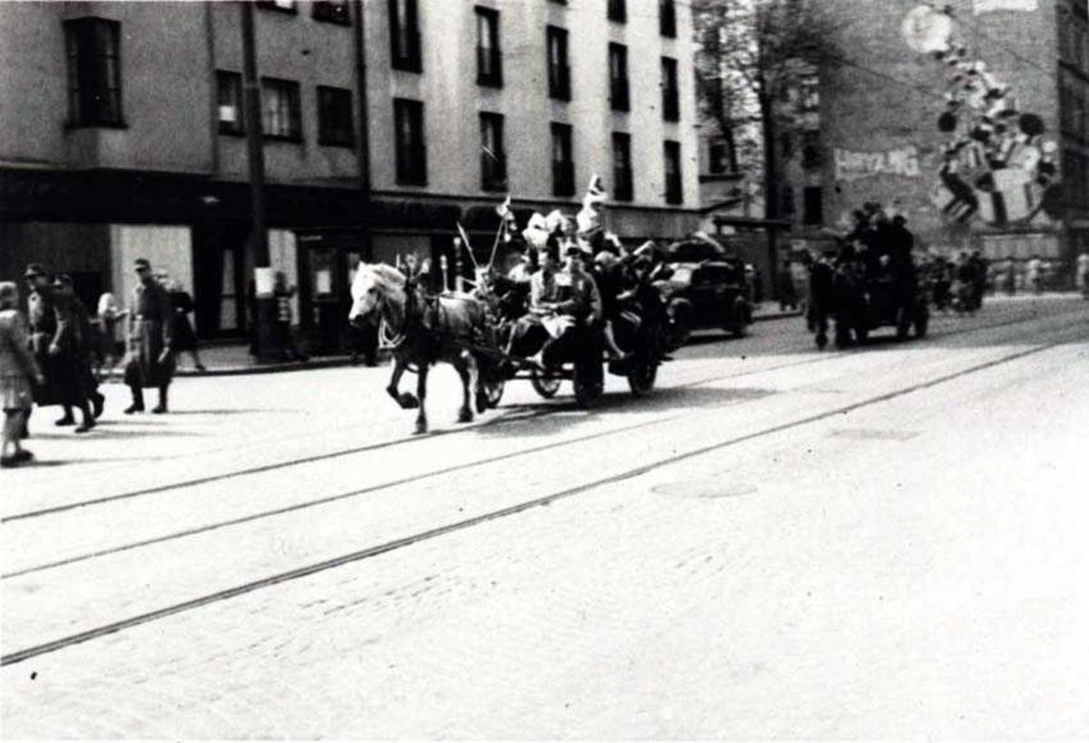 To hester med hver sin vogn i en bygate. Flere personer i vognene og på fortauet på siden. En bil og bygninger i bakgrunnen.