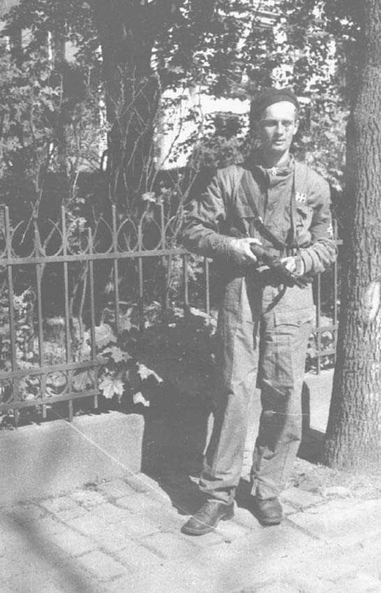 En person. Mann. Står i uniform, foran gjerde og holder et våpen i ene hånden.