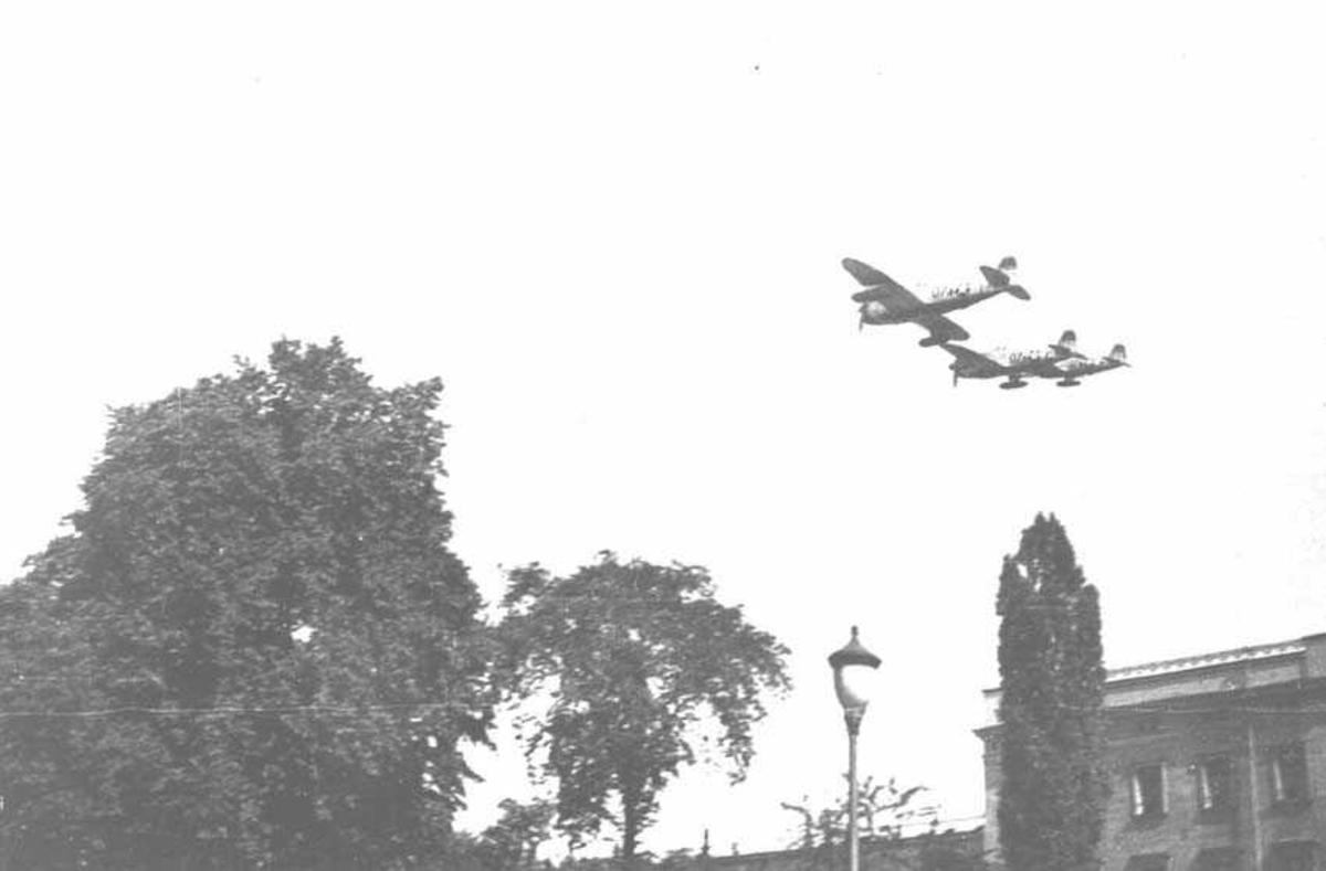 Tre fly på himmelen. Litt av en bygning på bakken. Flytype P-47 Thunderbolt
