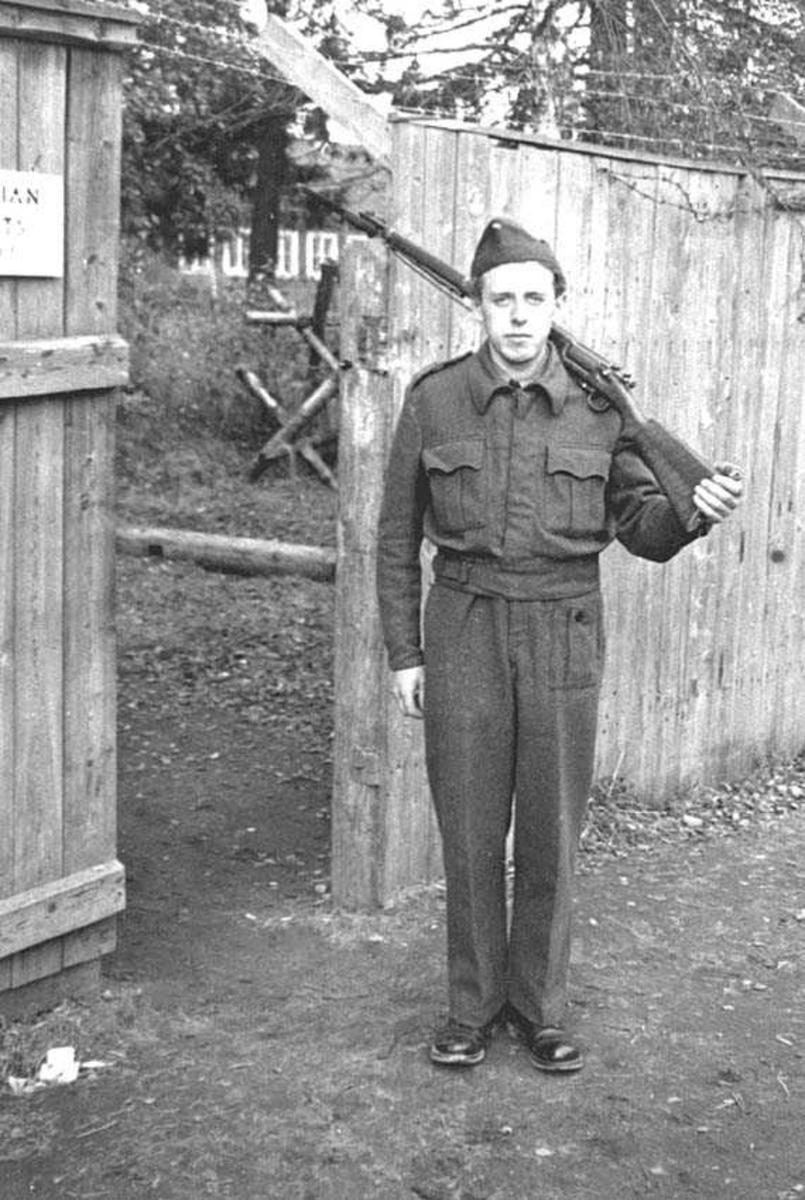 En person i militæruniform. Mann. Står foran en port. Har et våpen over skuldrene. Høyt plankegjerde med piggtråd øverst.