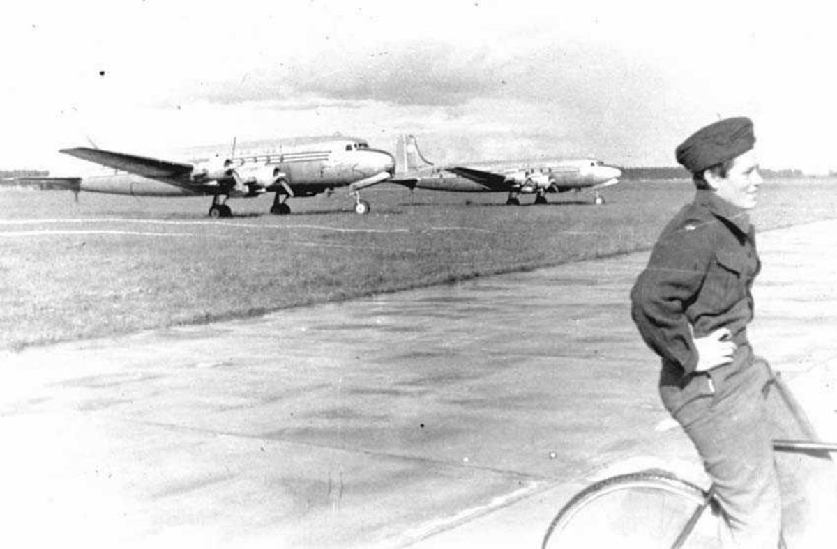 En person sitter på en sykkel. Mann i militæruniform. To fly i bakgrunnen (muligens Douglas C-54 Skymaster transportfly).
