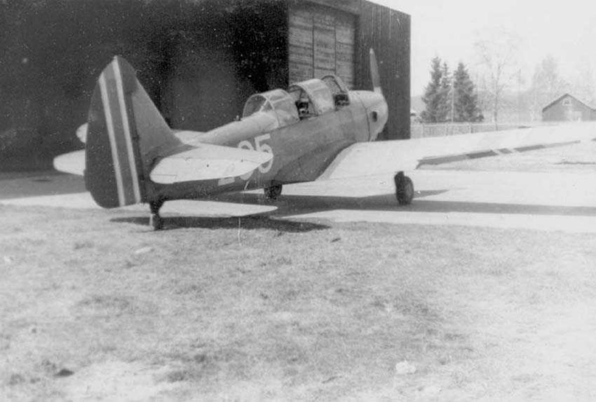 Et fly på bakken. Fairchild Cornell. Sett bakfra. Står utenfor en hangar. Bygning i bakgrunnen.