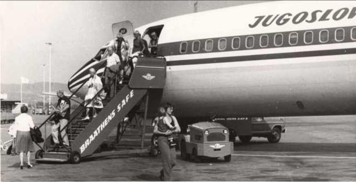 Et fly på bakken. Boeing 727-2H9. YU-AKG. Flere personer på vei ut av flyet.