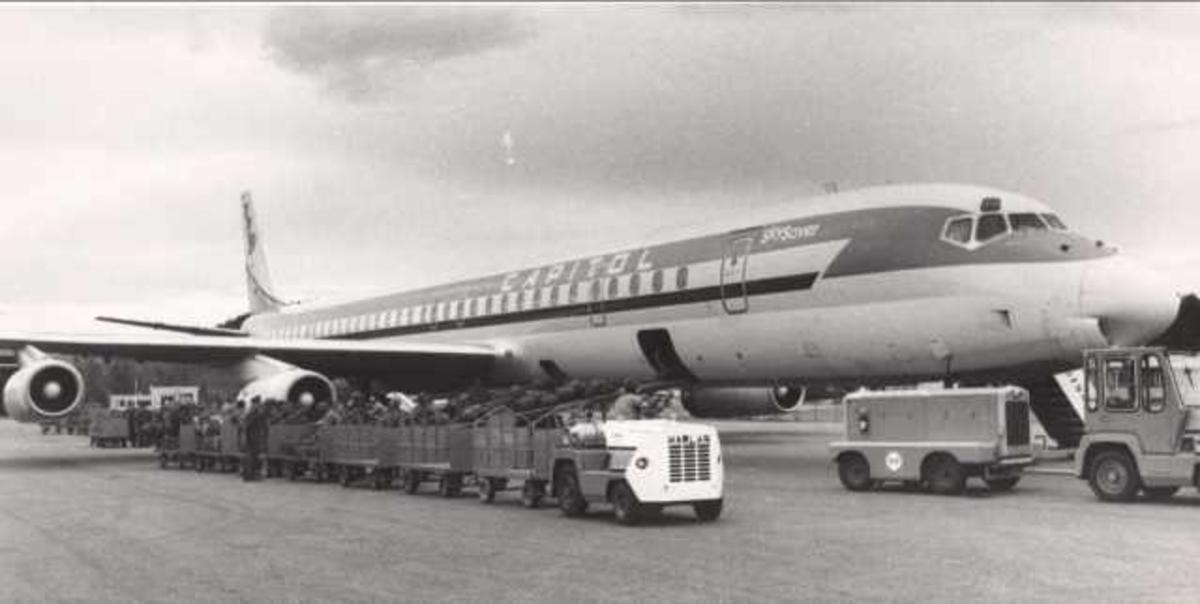 Ett fly på bakken. Douglas DC-8. Flere personer ved flyet.