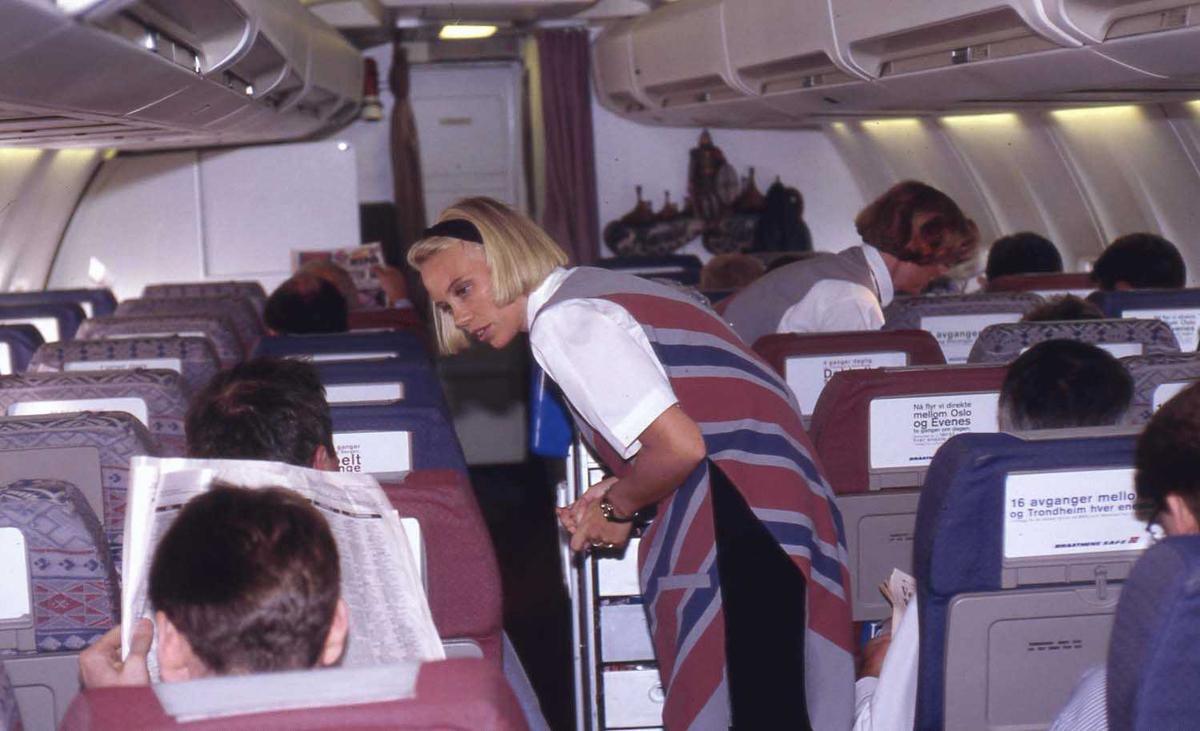 Ett fly i luften. To flyvertinner i midtgang, flere passasjerer sittende.