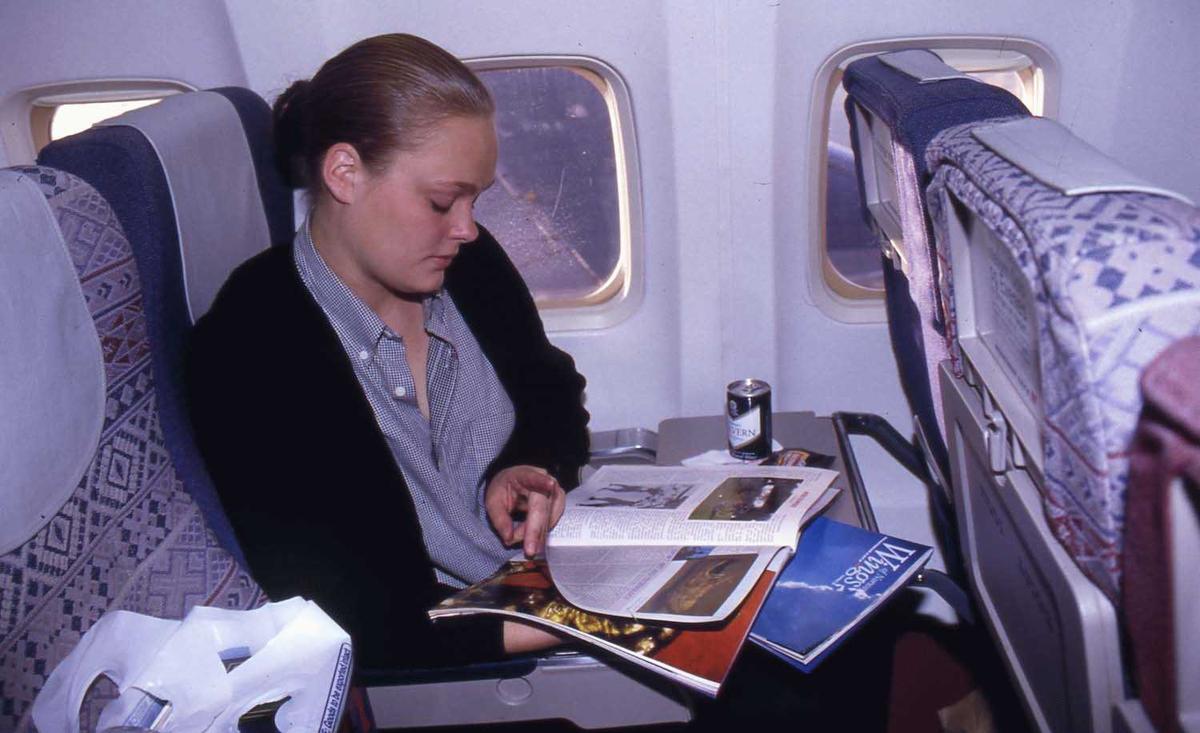 Ett fly i luften. En passasjer sittende ved vindu.