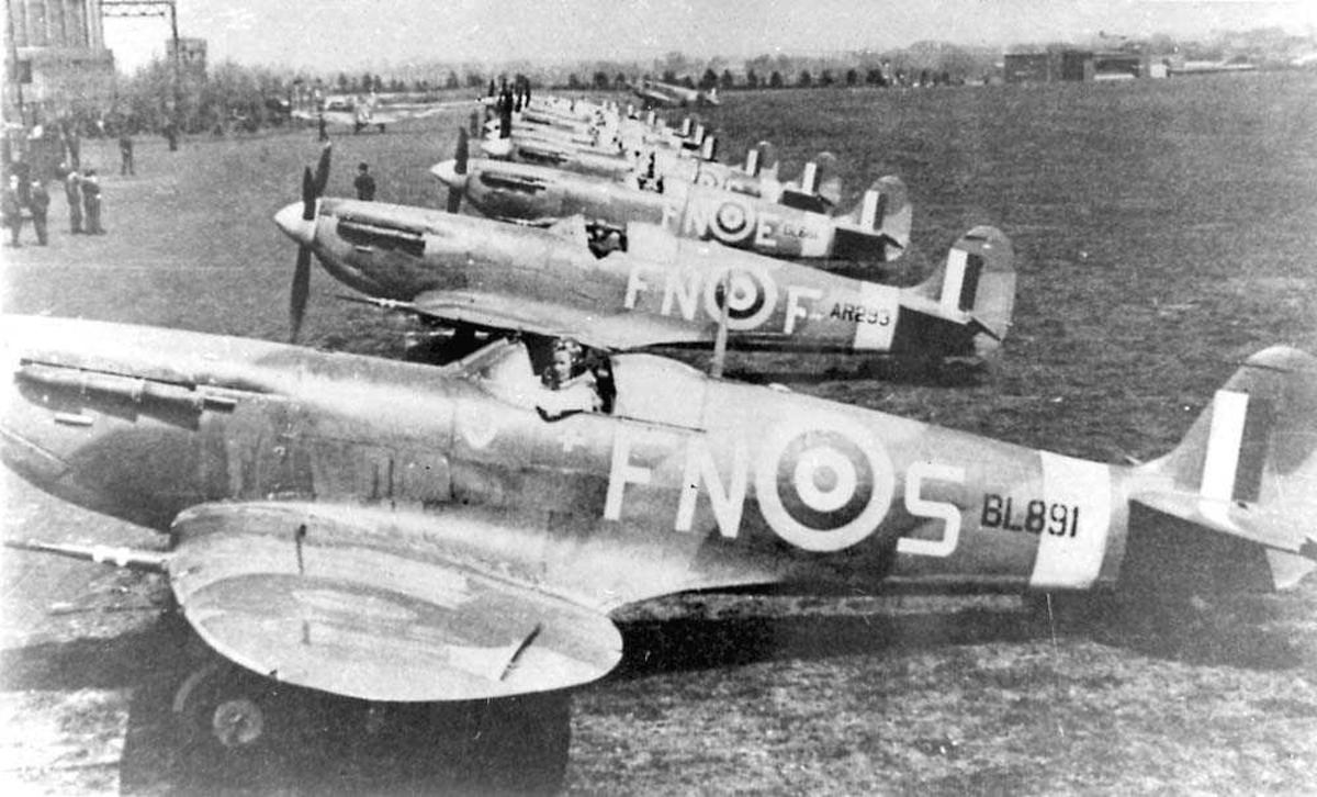 Flere fly på bakken. Spitfire MK V B. En person sitter i cockpiten på hvert fly. Personer og bygninger ved siden av flyene.