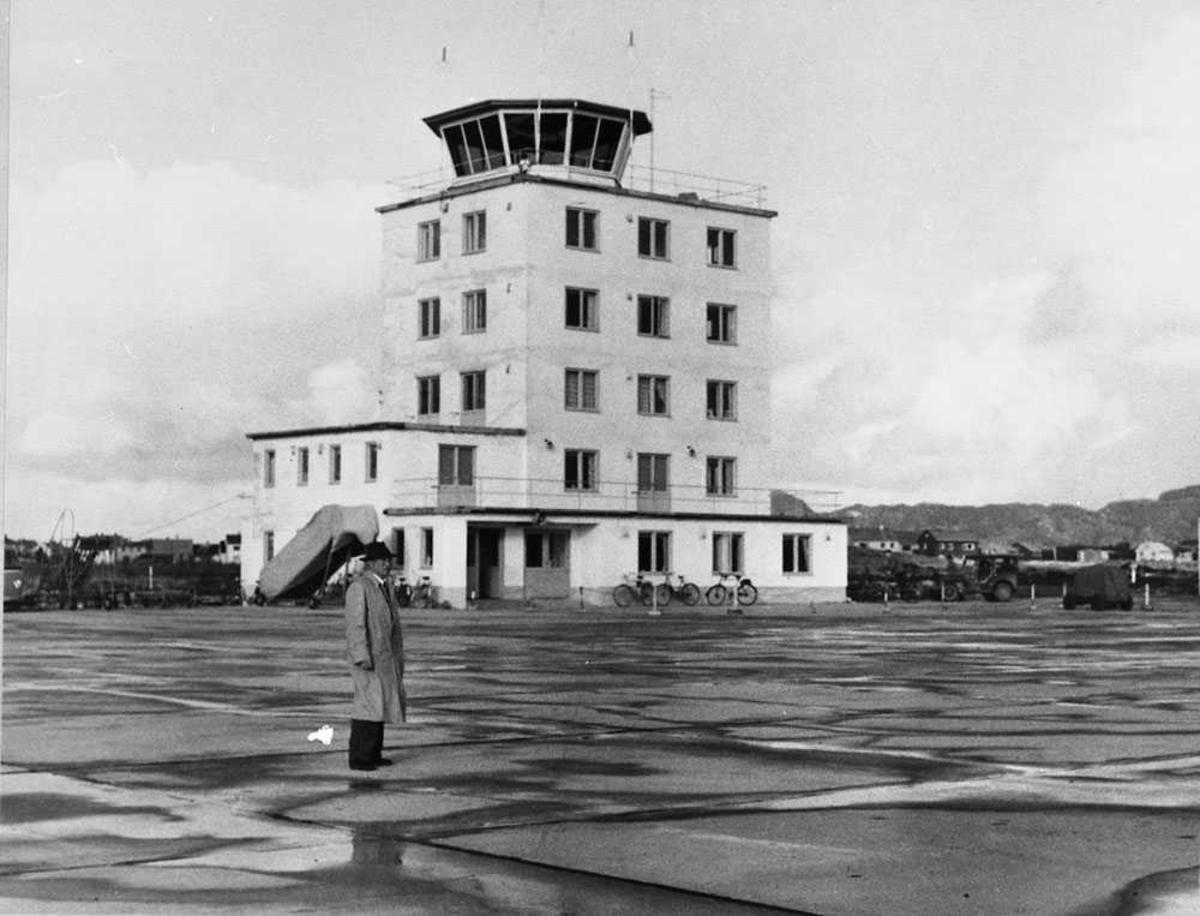 Lufthavn. Ekspedisjonsbyggningen med kontrolltårnet. En person i forgrunnen.