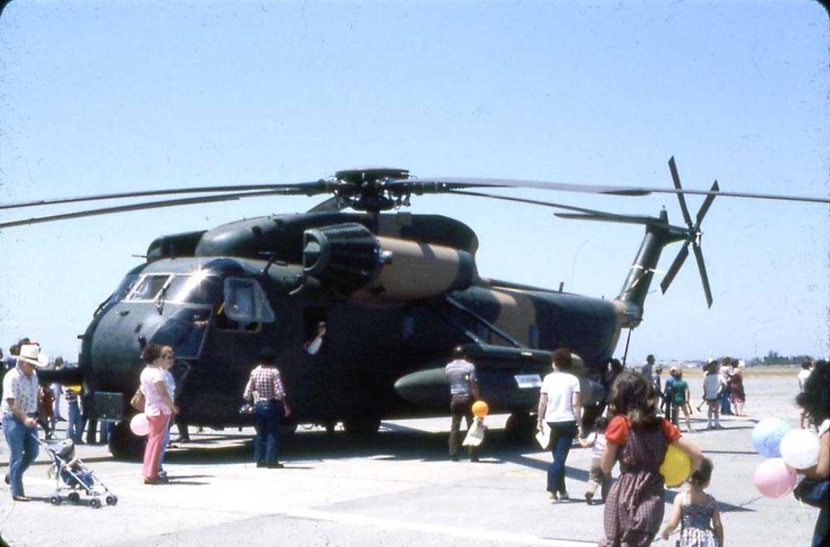 Lufthavn. Ett helikopter på bakken, Sikorsky S-80 (CH-53E) Super Stallon. Flere sivile personer rundt helikoptret (ant. flyutstilling).