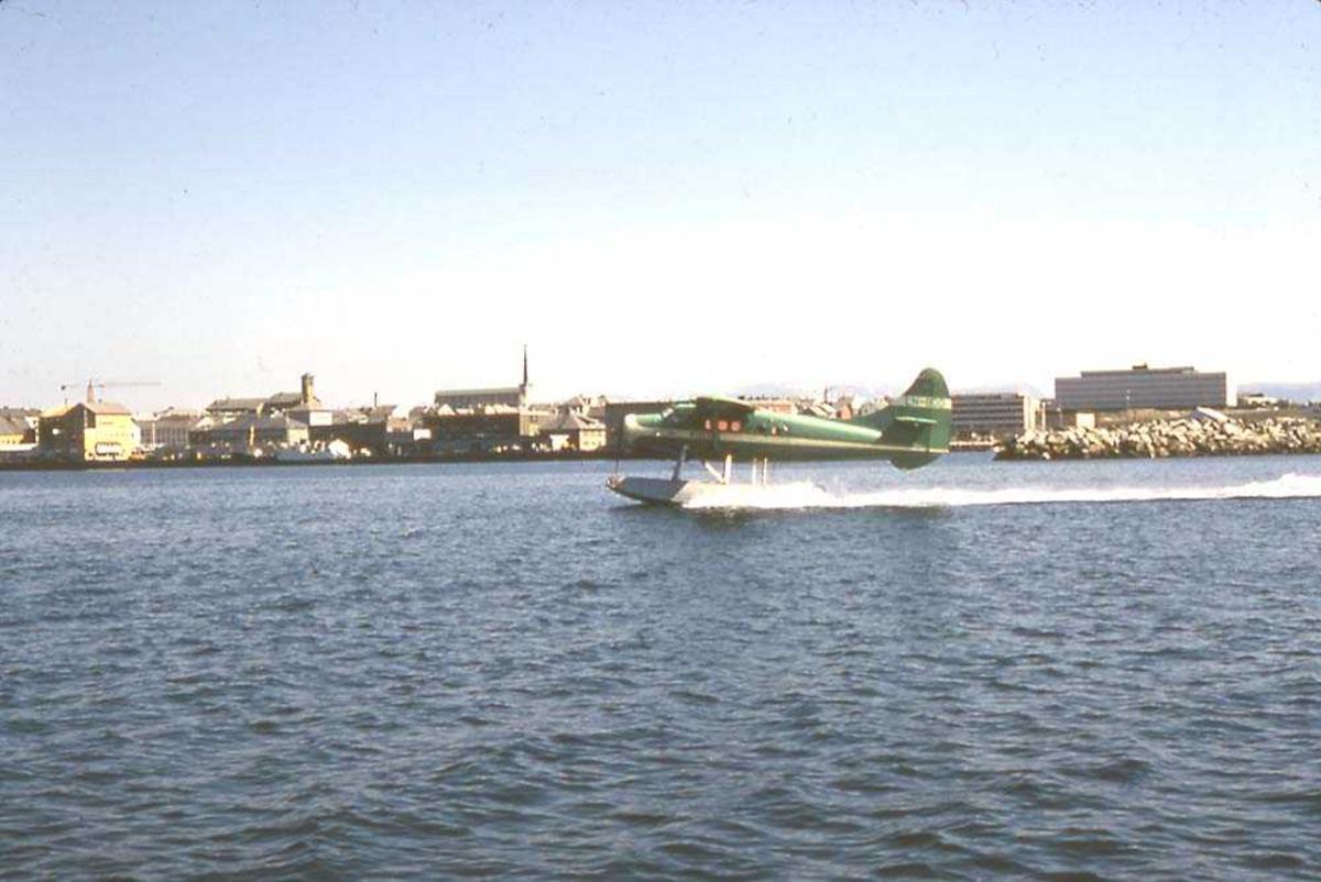 Ett fly i fart på vannet, DHC-3 Otter LN-BDD fra Widerøe. Bygninger/by (Bodø) i bakgrunnen.