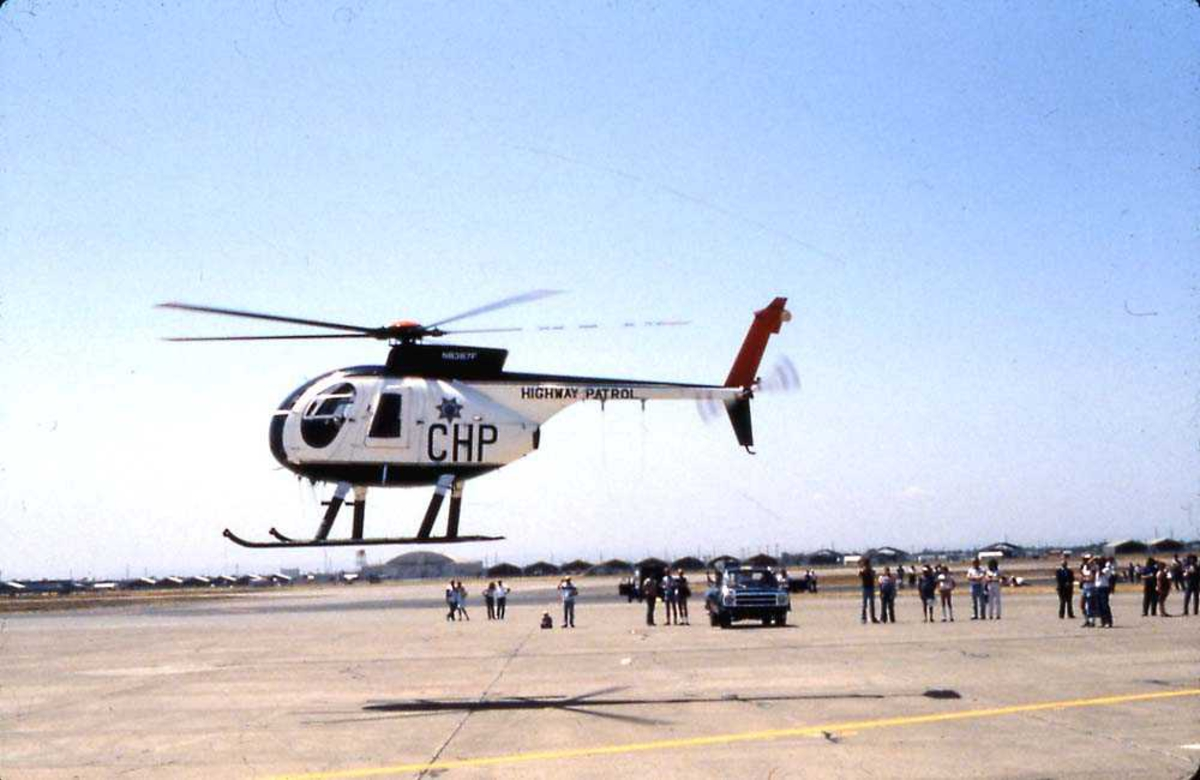 Flystevne. Ett helikopter i luften like over bakken, Hughes 500. Flere personer og et kjøretøy på bakken bak helikoptret.