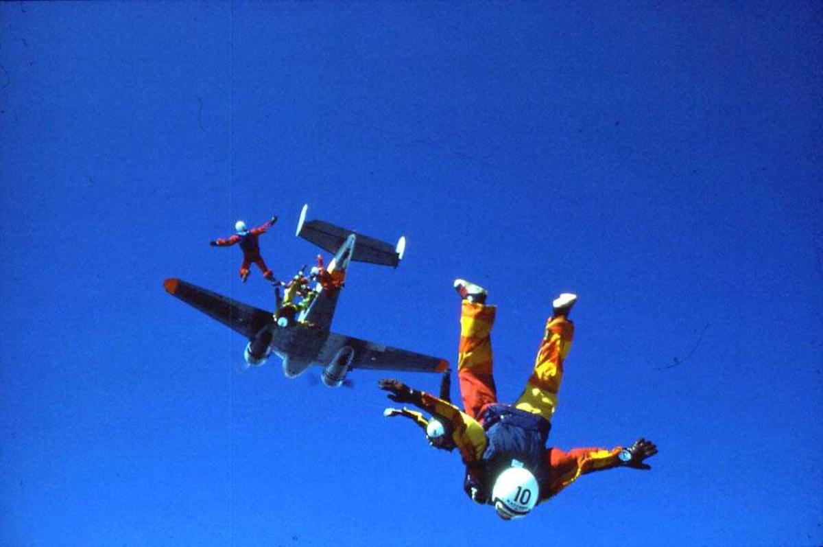 Luftfoto. Flere fallskjermhoppere som hopper ut av et fly.
