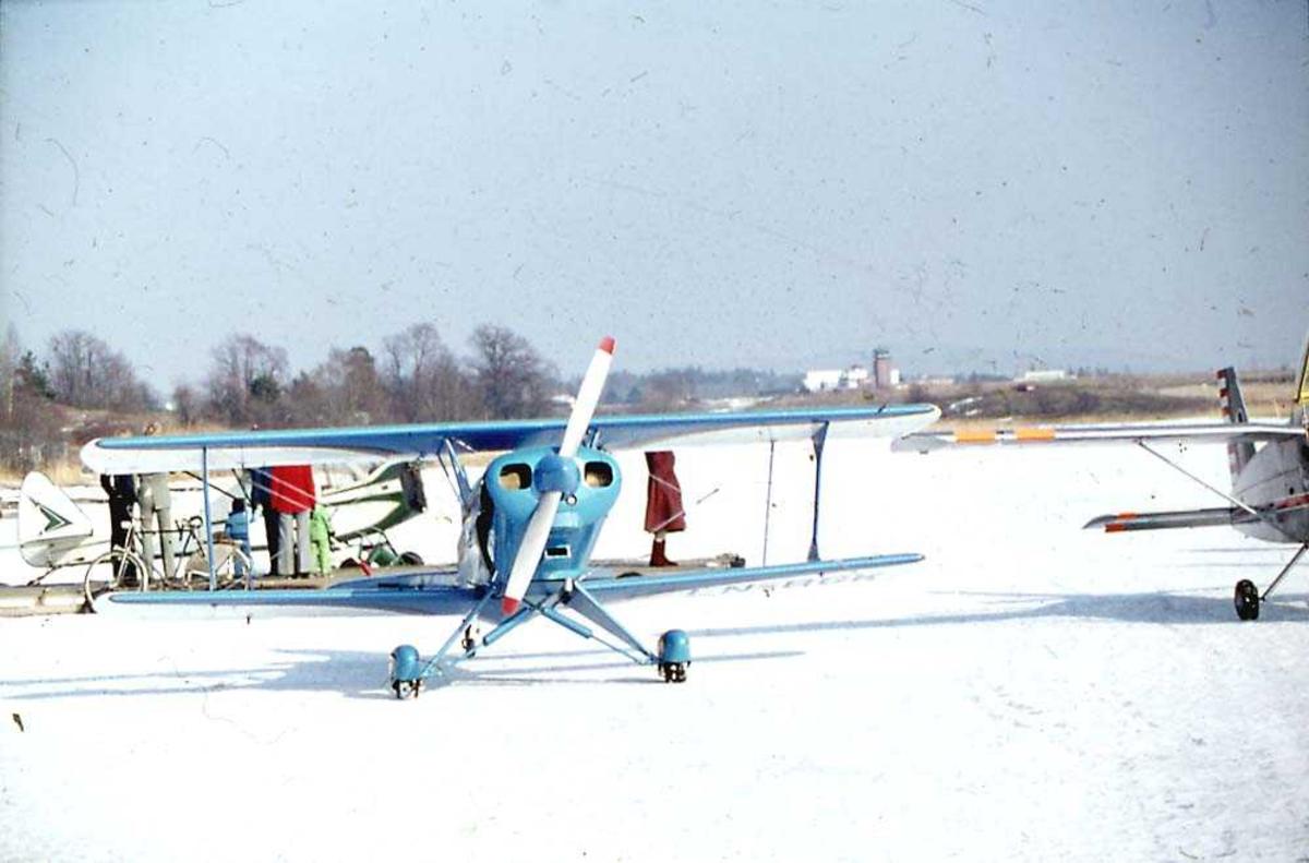 Ett fly på bakken, EAA Acro Sport, LN-BGK. I bakgrunnen Piper PA-18 Super Cub LN-VYP uten motor og vinger. Til høyre Malmö Flygindustri MFI-9