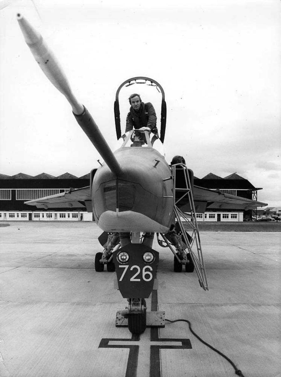 Lufthavn. Ett fly på bakken, Jaguar G.R. Mk 1. En person i cockpitåpningen. Bygning i bakgrunnen.