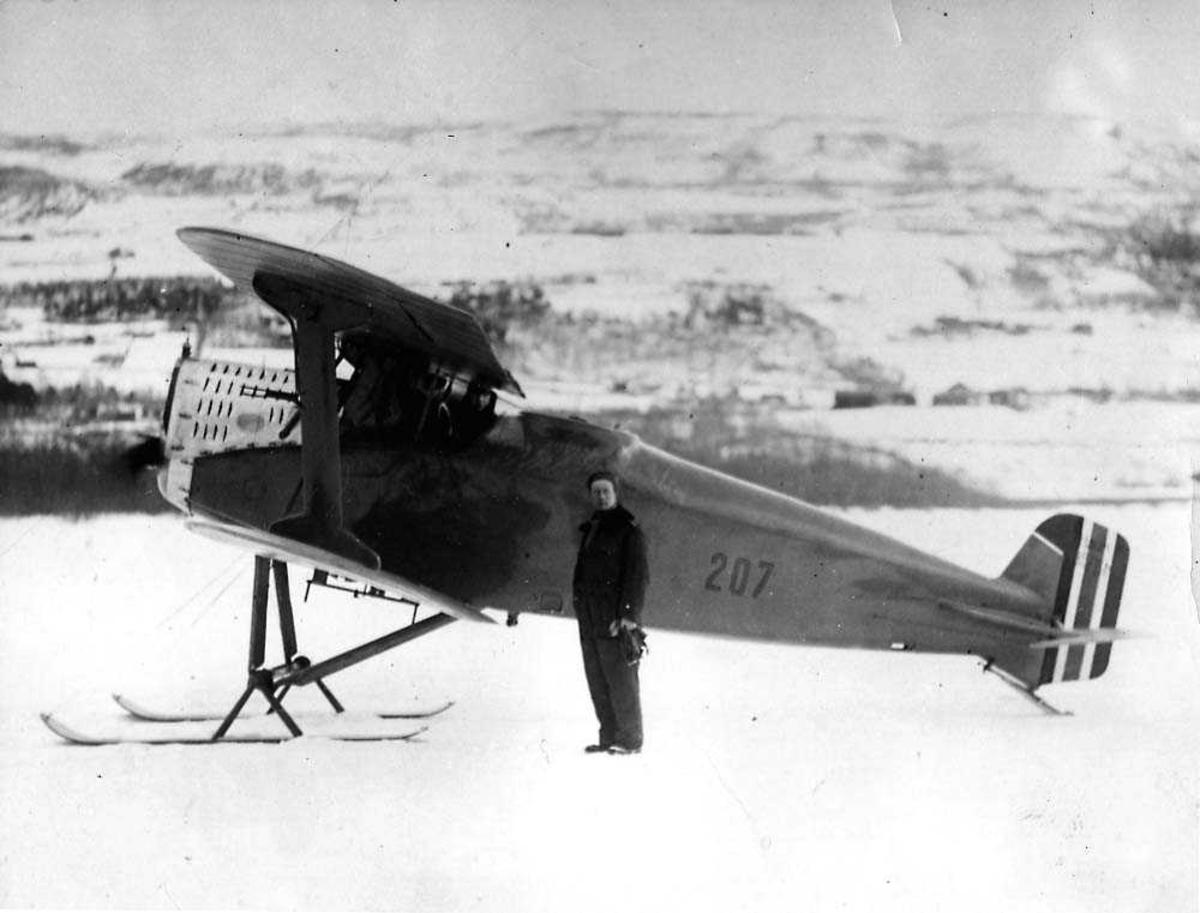 Ett fly på isen med flotører, lisensbygd FF 7 Hauk. En person står ved flyet.