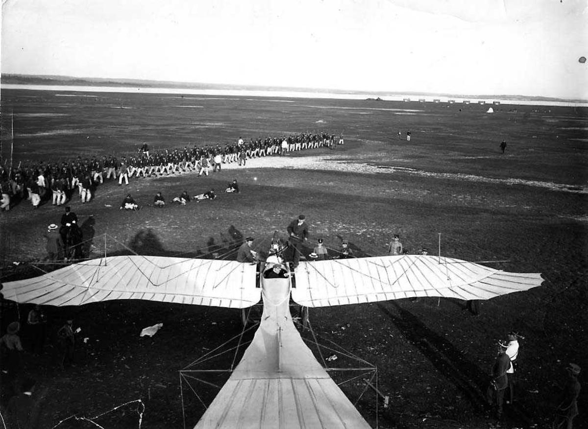 """Ett fly på en åpen plass, Rumpler Taube """"Start"""". Flere personer rundt flyet. En militærtropp i bakgrunnen."""