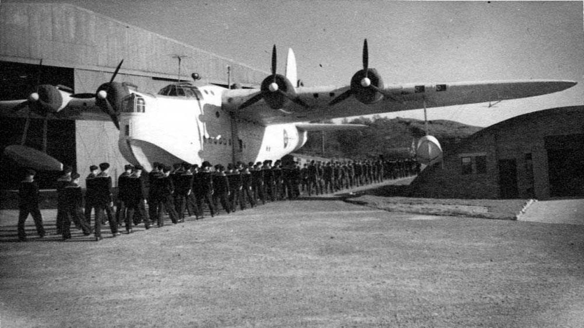 Lufthavn. Ett fly på bakken, Short Sunderland. En militærtrop masjerer fordi flyet. Bygninger i bakgrunnen.