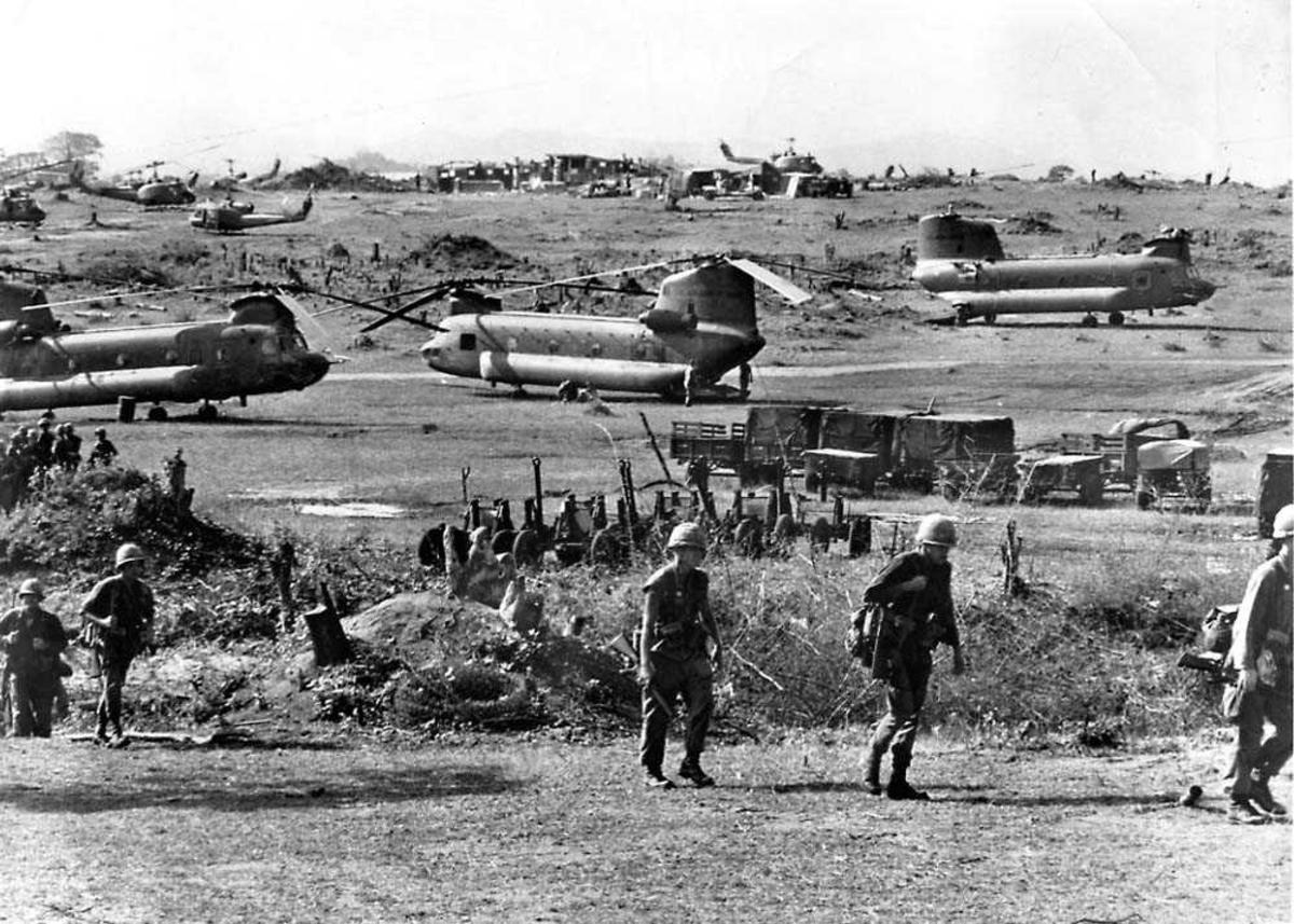 Helikopterbase. Flere helikoptere på bakken. Militære kjøretøyer og mannskap.
