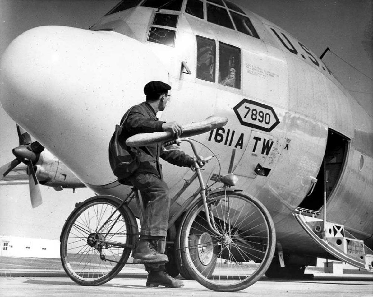 Lufthavn. Ett fly på bakken, Lockheed C-130H Hercules fra US Air Force. En person på sykkel foran flyet.