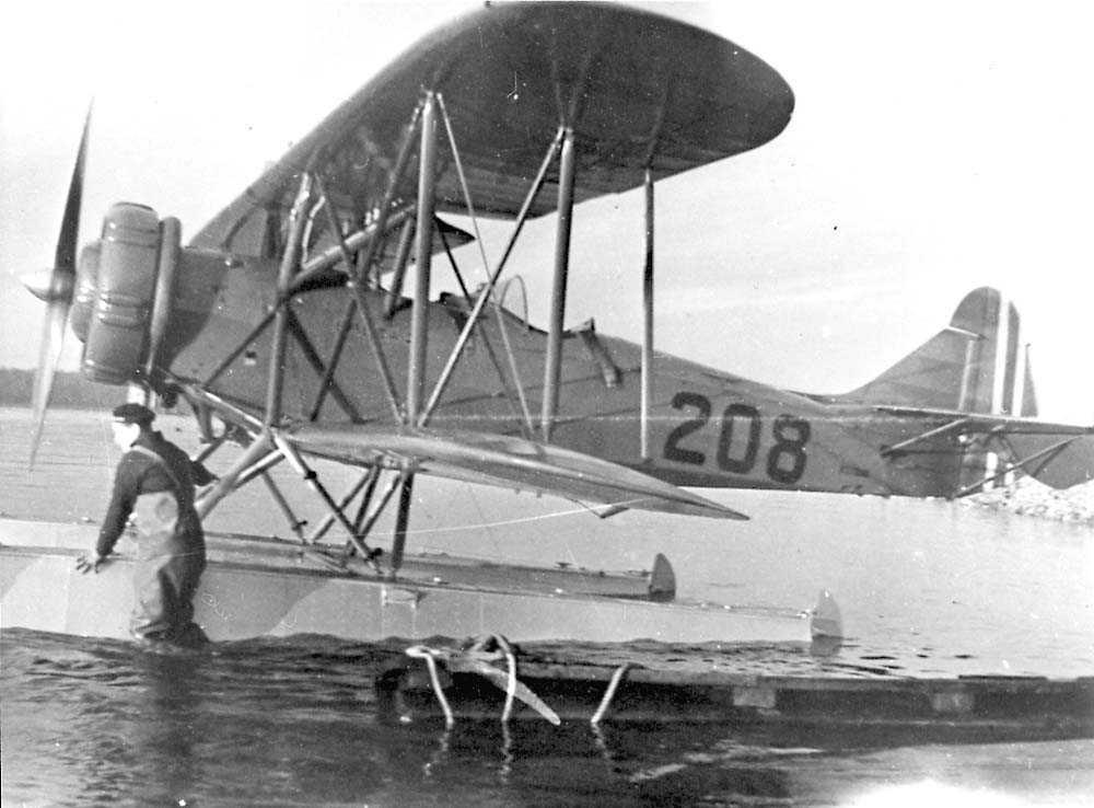 Ett fly på vannet, Breda Ba.28.med EDO flotører. En person står i vannet ved flyet.