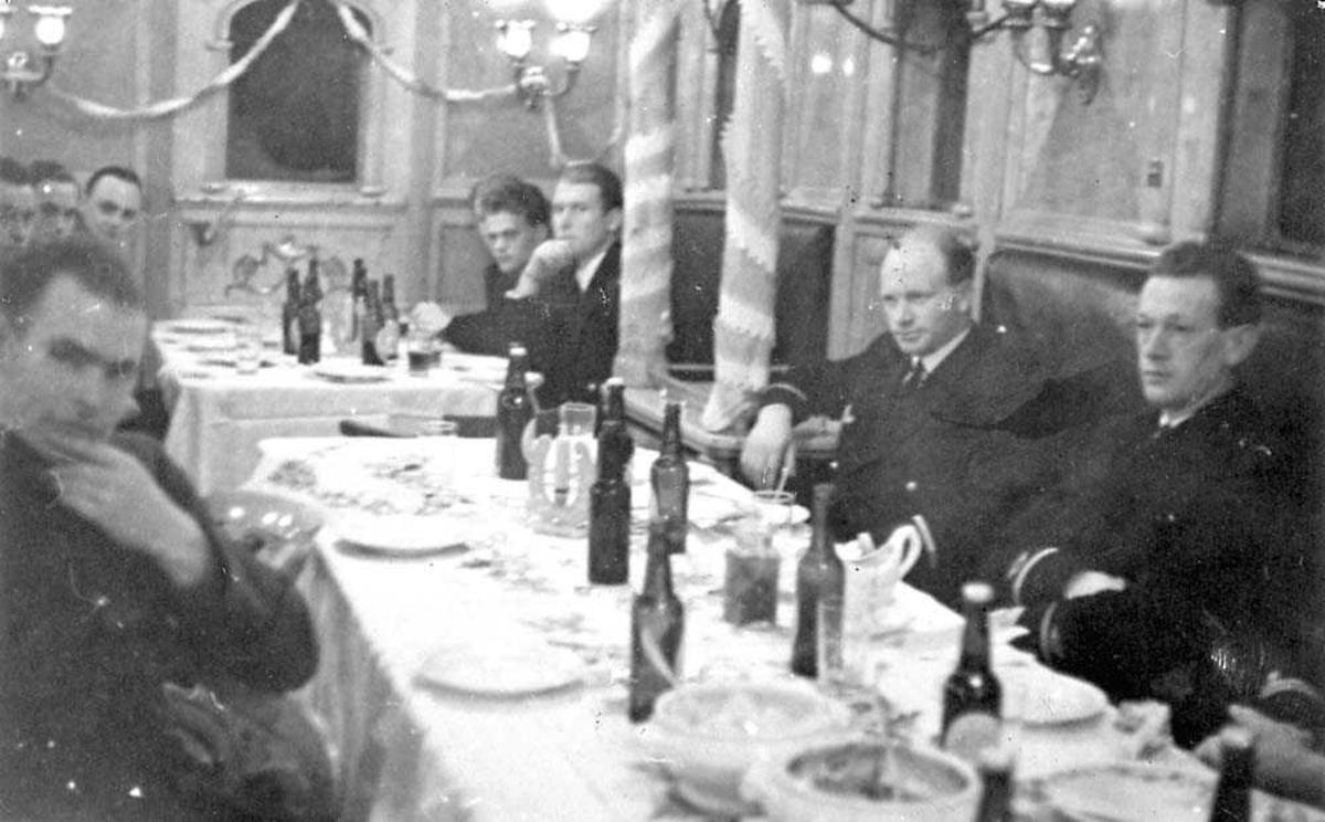 Flere personer som sitter rundt to bord som dekket.