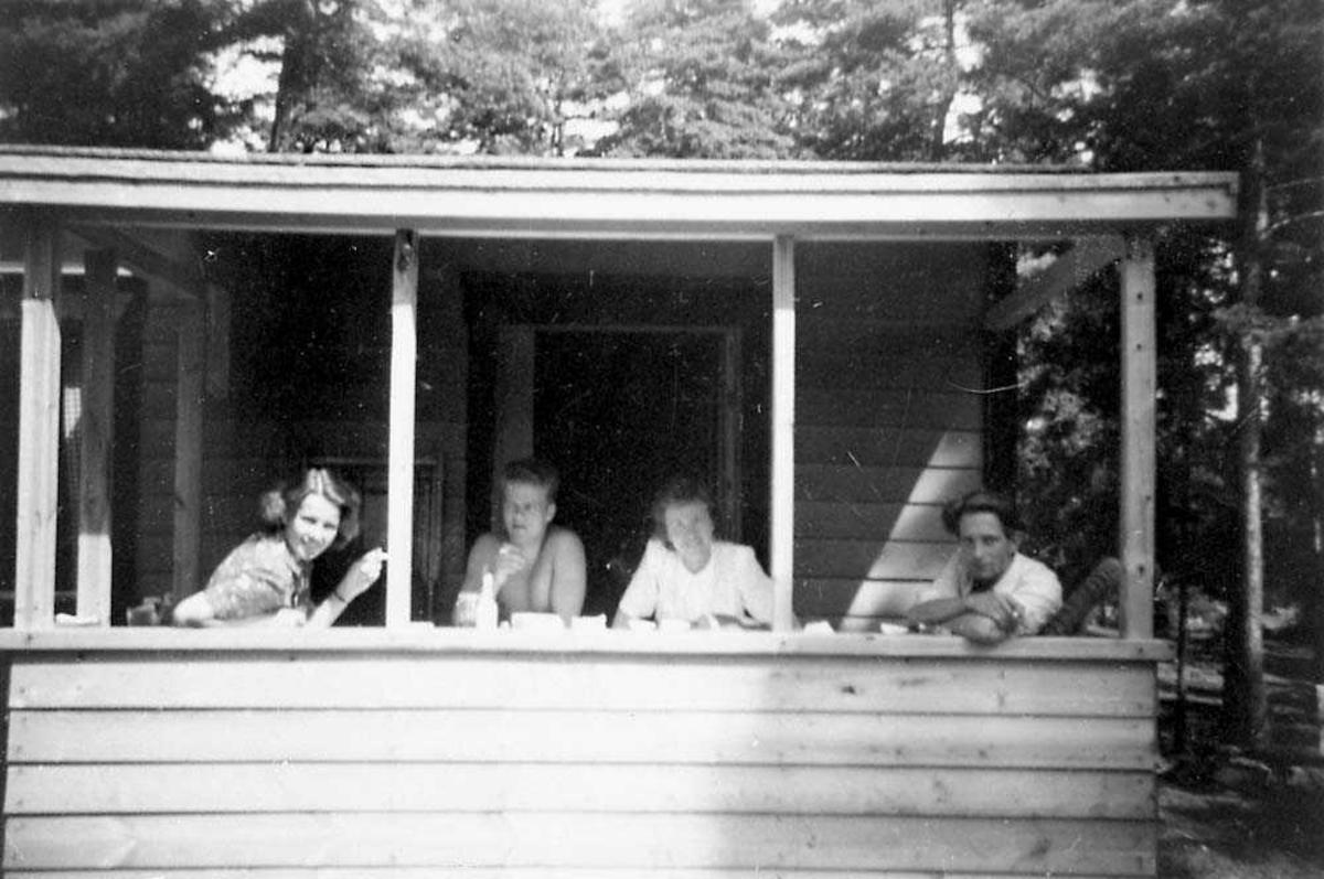 Portrett. Fire personer som sitter i ei bu/hytte og røyker.