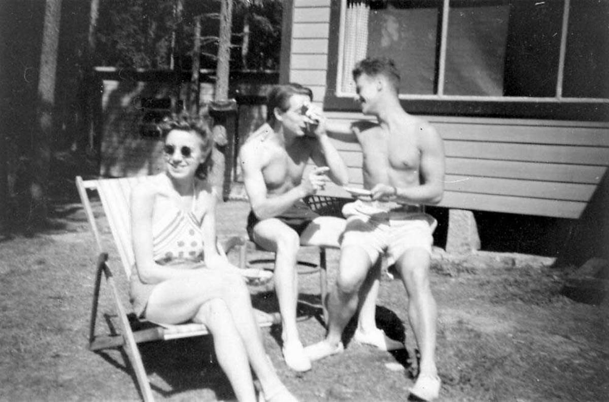 Portrett. Tre personer. To menn og en kvinne som sitter og har badedrakt på seg. Bygning i bakgrunnen.