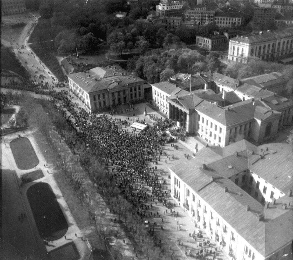 Luftfoto. By. Folkemengde på en åpen plass foran en bygning.