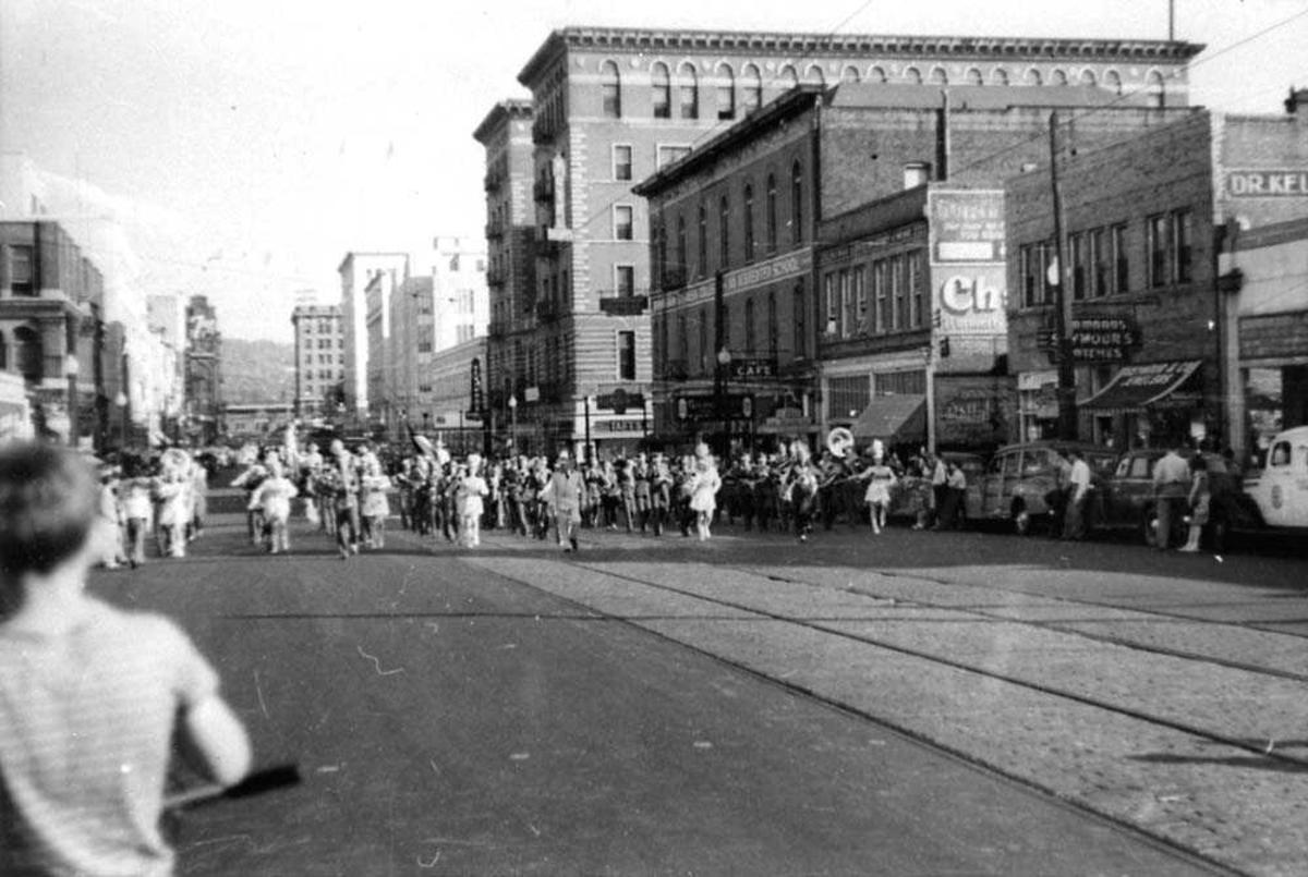 Rodeo opptog i en bygate. Flere personer som står å ser på. Bygninger i bakgrunnen.