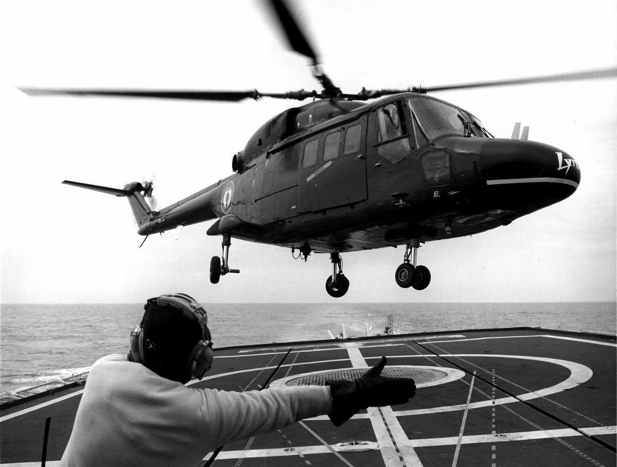Ett helikopter i luften, like over helipad på skipsdekk, en person i forgrunn, dirigerer landing. Westland Lynx HAS Mk.2