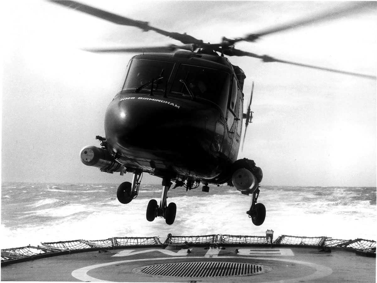 Ett helikopter i luften, like over helipad/skipsdekk. 2 torpedoer hengende på hver sin side. Westland Lynx (ukjent Mk)