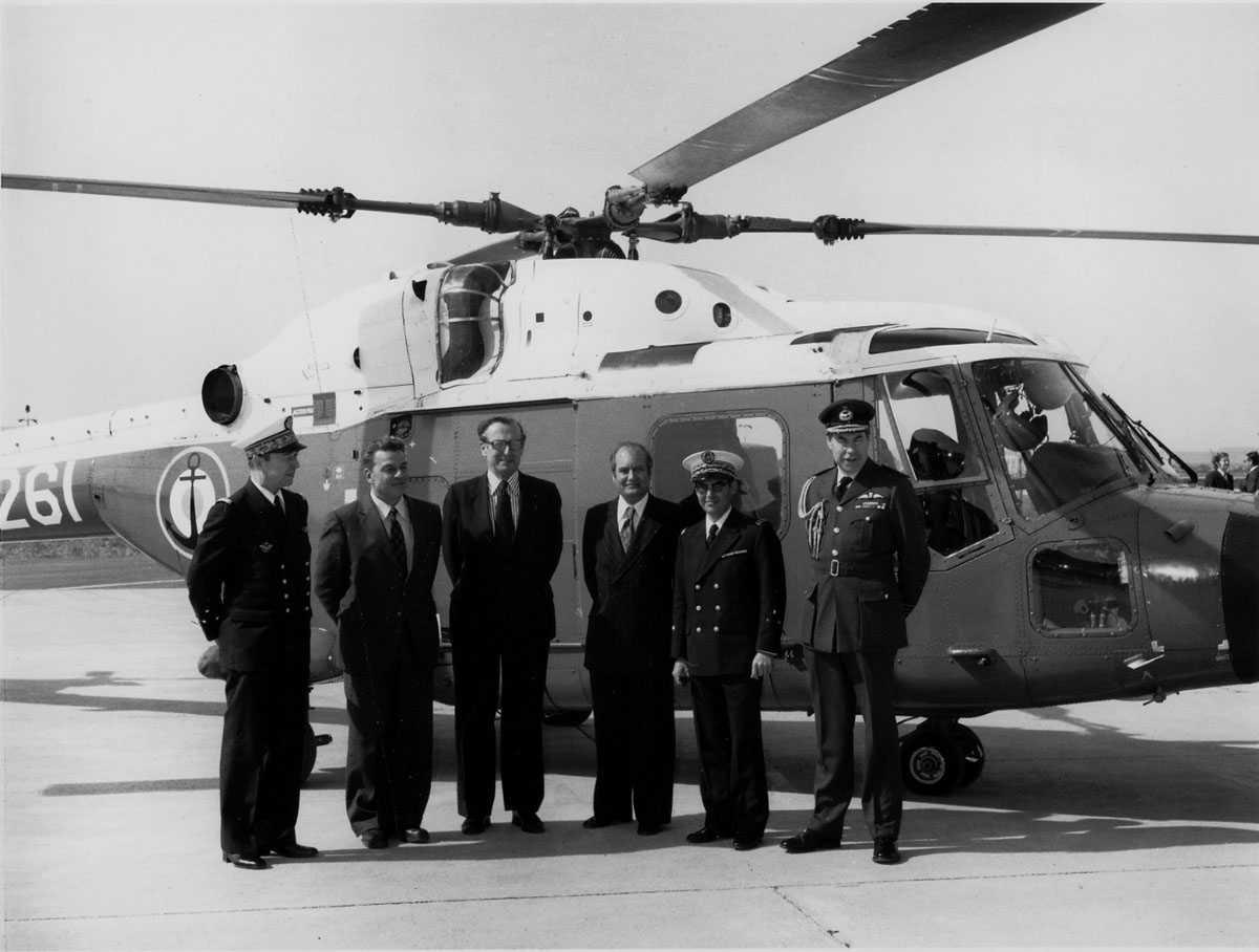 Ett helikopter på bakken. Westland Lynx HAS Mk.2, synlig merket 261. Tre offiserer og tre sivile foran helikoptert.