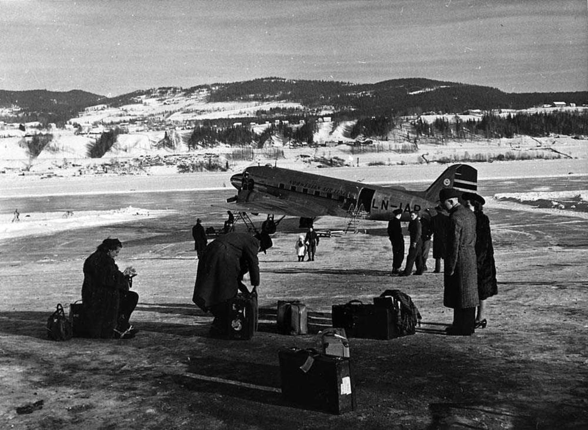 """Ett fly på en islagt innsjø, Douglas DC-3/C-47 Dakota LN-IAP """"Halvdan Viking"""" fra DNL. Flere passasjerer og kofferter i forgrunnen. Fjell i bakgrunnen. Snø på bakken."""