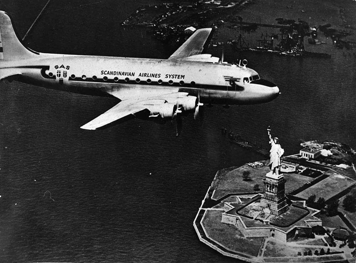 Luftfoto. Ett fly i luften, Douglas DC-4/C-54 Skymaster fra SAS som flyr over frihetsgudinnen.