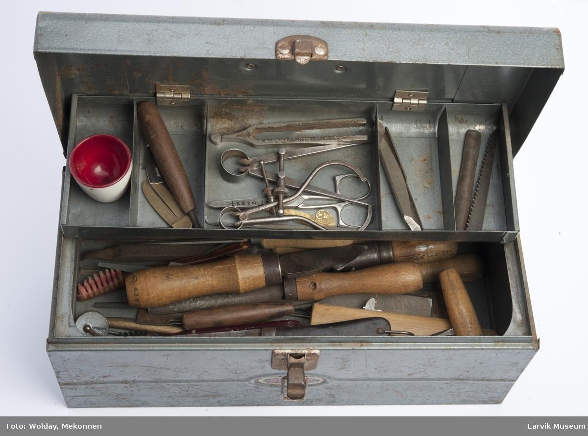 Verktøykassen består av  diverse verktøy som Kniver, filer, syl skjærejern, børster, tannlegeutstyr, passer, blyant, eggeglass, spatel etc.  Verktøykasse m. liten hank