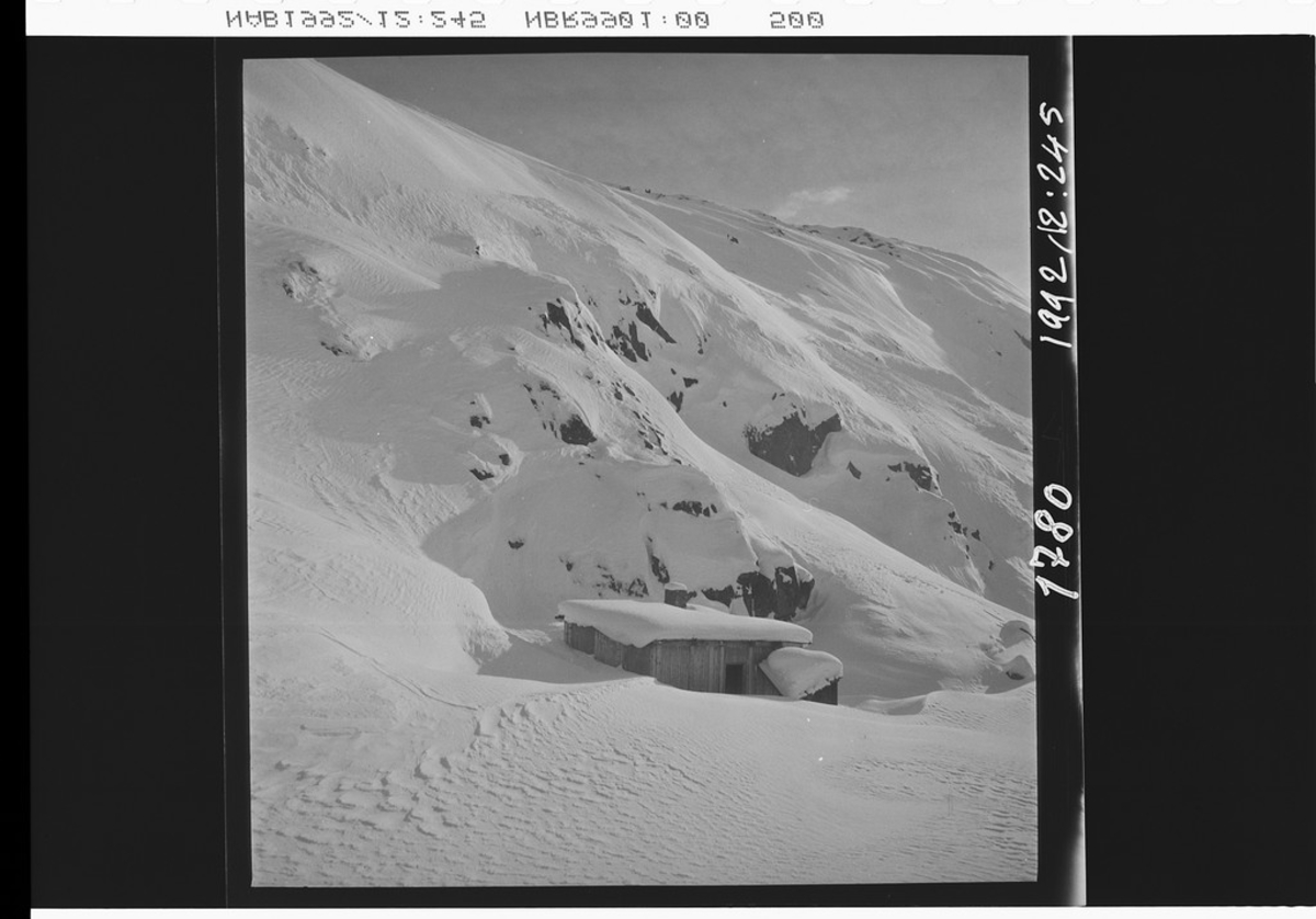 Nedsnødd hytte ved bergkant.