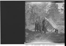 Speiderleir. Tre speidere utenfor et telt.