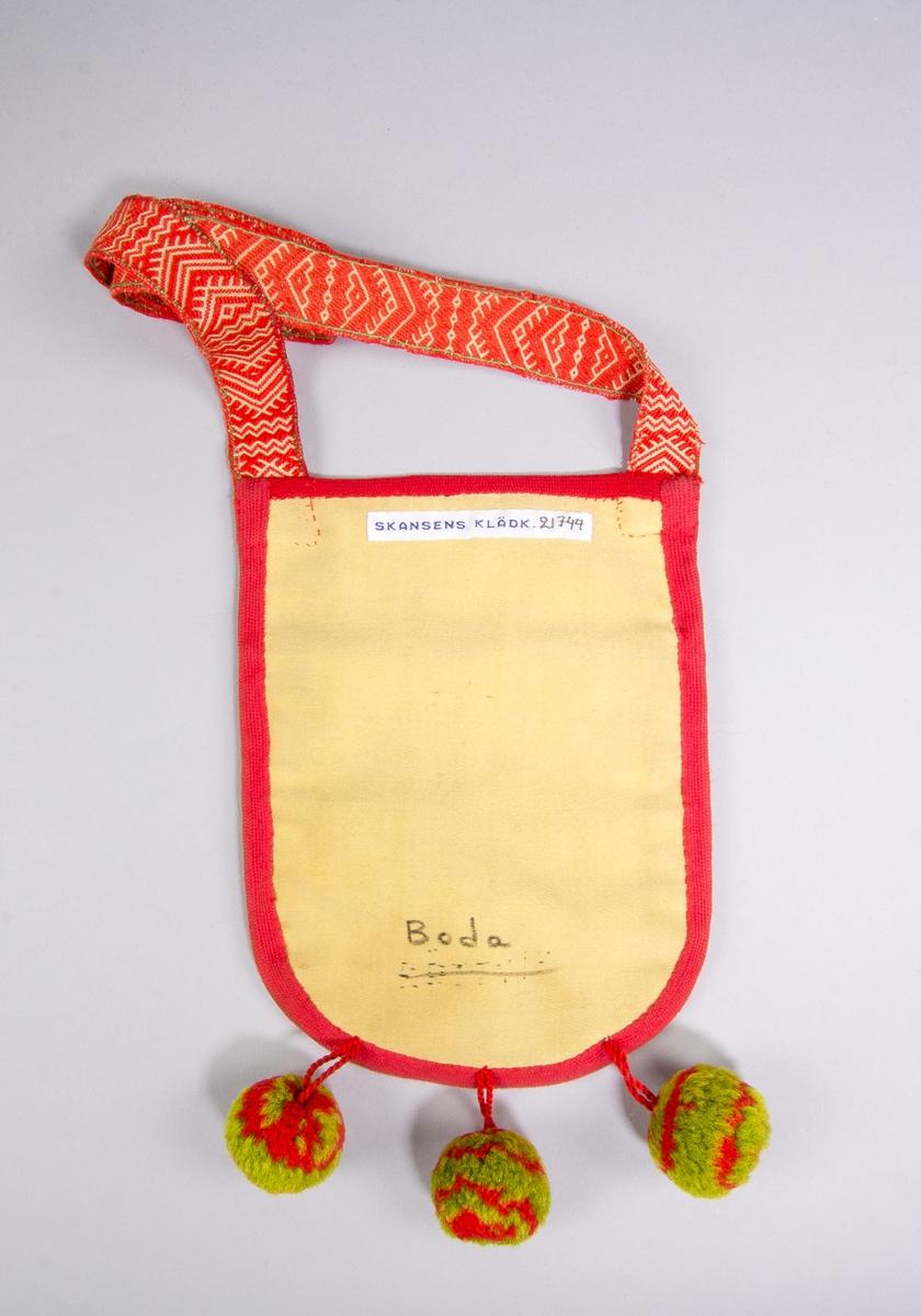 """Kjolsäck till dräkt för kvinna från Boda socken, Dalarna. Modell med avskuret framstycke. Tillverkad av vitt fårskinn med applikationer av ylletyg, kläde, i rött och grönt, fastsydda med maskinsöm med gul tråd. Centralt placerad fyrbladig blomma med fyrdelade cirklar och rundlar runtom. Broderi utfört med gult bomullsgarn: sticksöm och plattsöm. Ovan applikationen en """"grind"""" flätad av rött och grönt ullgarn samt smala remsor vitt fårskinn. Kantat runtom med rött diagonalvävt bomullsband samt ylleband. I nederkanten fäst tre bollar av rött och grönt ullgarn. Foder av rött bomullstyg, tuskaft. Överstycke av rött kläde. Bakstycke av gult bomullstyg, mollskinn. Axelband handvävt, med plockat mönster av rött ullgarn på vit botten, en hake av mässingstråd."""