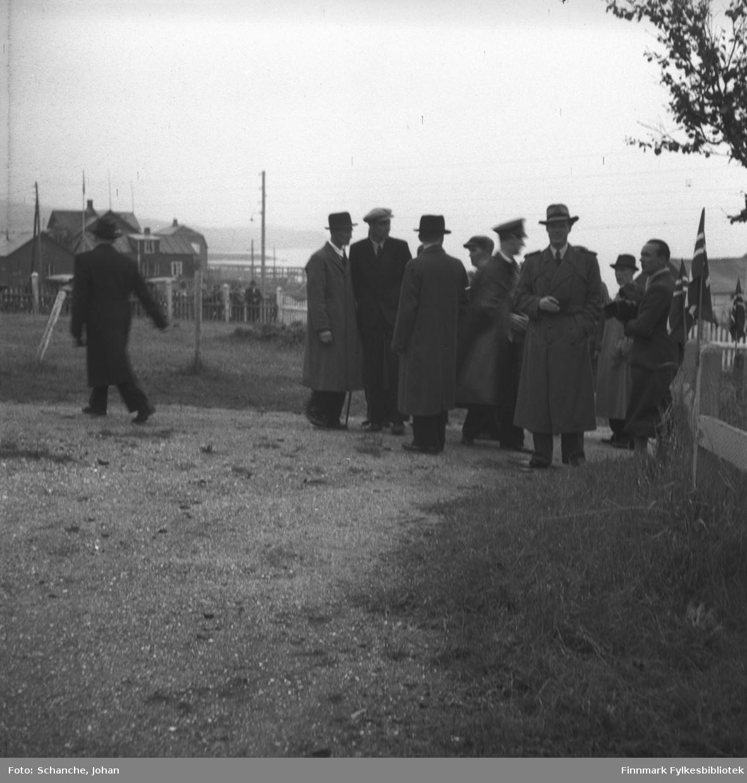 Kongebesøk:  Kong Haakon VII besøker sykehuset i Vadsø. Kongen med følget står ved hagegjerden til sykehuset. Det ser ut som om de venter på noen. Fylkesmann  Hans Gabrielsen går til venstre bort fra gruppen.