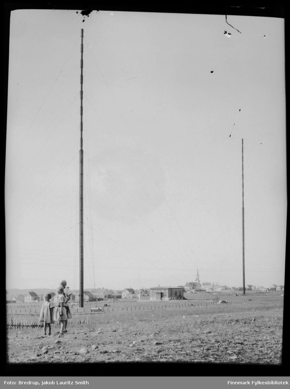 Tre jenter står foran kringkastingshuset og radiomastene.  Bak kringkasting en del av byen, kirke til høyre.
