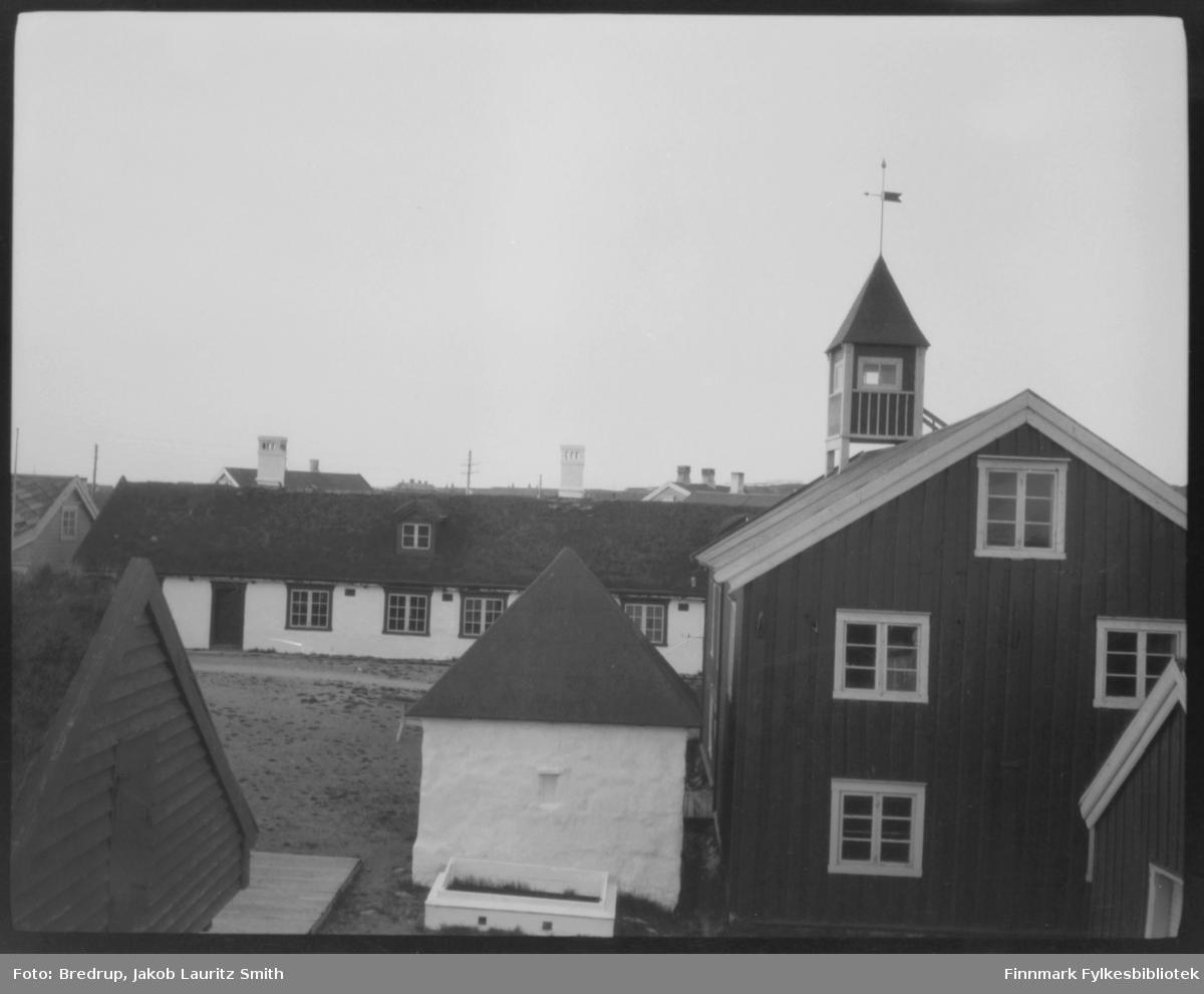 Bygninger på Vardøhus festning.  Det lille hvite huset midt i bildet er aggregathuset, opprinnelig brønn.  Huset med tårn er depotet ('proviant- og materialhus').  I bakgrunnen med torvtekt tak og arker garnisonsbrakken, også kalt kasernen eller 'slaveriet'.