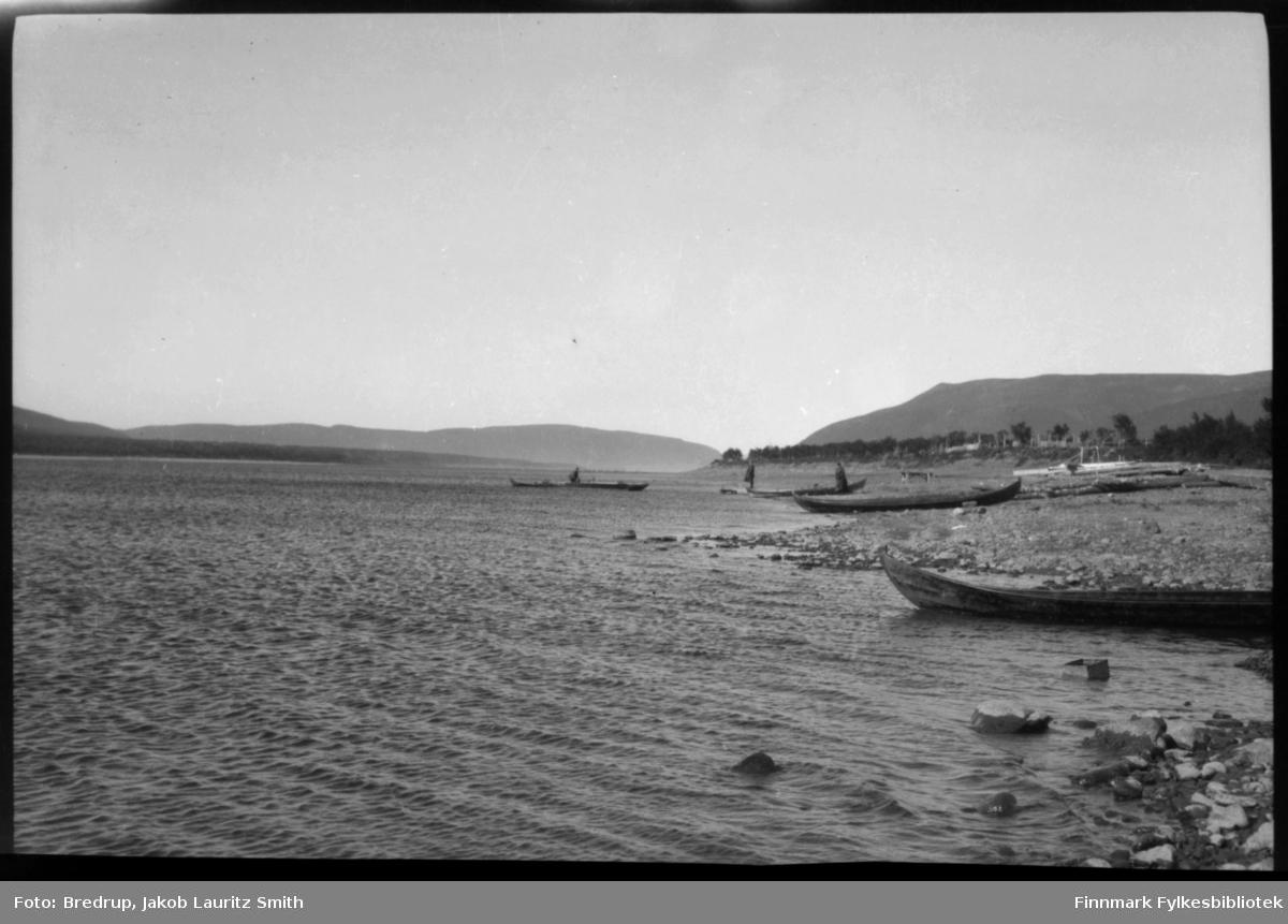 To personer står og venter på elvebredden, flere elvebåter er trukket opp på land.  En levebåt med fører på vei inn.  Antakelig er dette Tanaelva, og to personer som venter på skyss over.