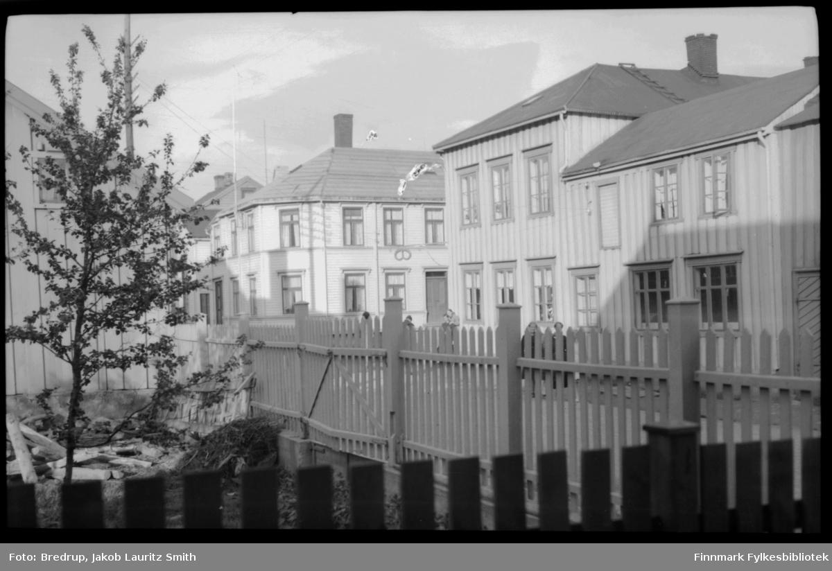 Fotografert i Vadsø sentrum.  Vi ser bygninger, gater, en inngjerdet hage.  Fra en av bygningene henger et bakeriskilt, dette er Henriksens bakeri.