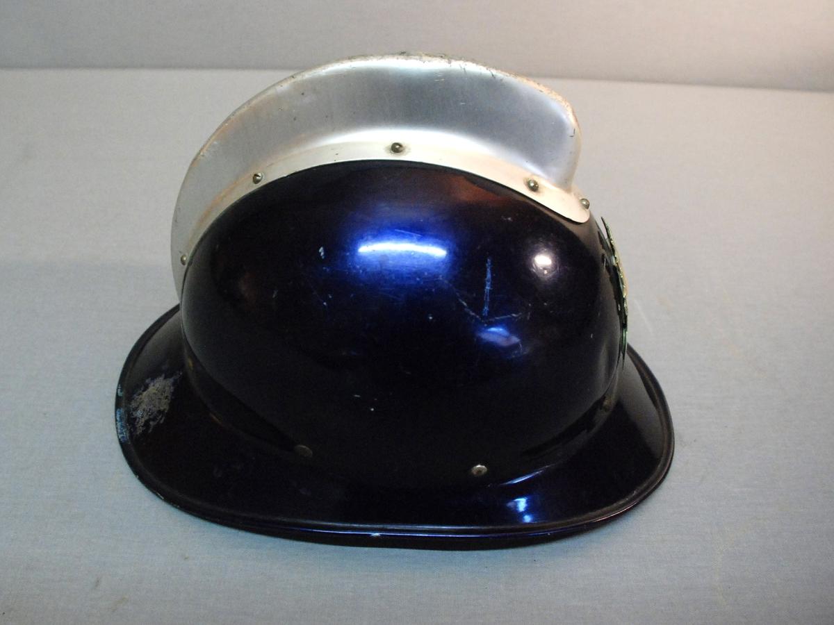 Brannhjelm i metall med brem rundt hele hjelmen, -smalest på sidene og bredere foran og bak. Hjelmen har blå farge. På toppen er satt på en kam av aluminiumfarget metall, skrudd til hjelmen. foran har hjelmen et aluminiumsmerke formet som Bergens byvåpen. Innvendig har hjelmen skinnfor festet til ettekstilbelagt gummiband som igjen er festet til hjelmens ytterfor, som er av lerret. På ytterforet er det 5 hemper med trykknapper. Hakereim i skinn, lukket med metallspenne.