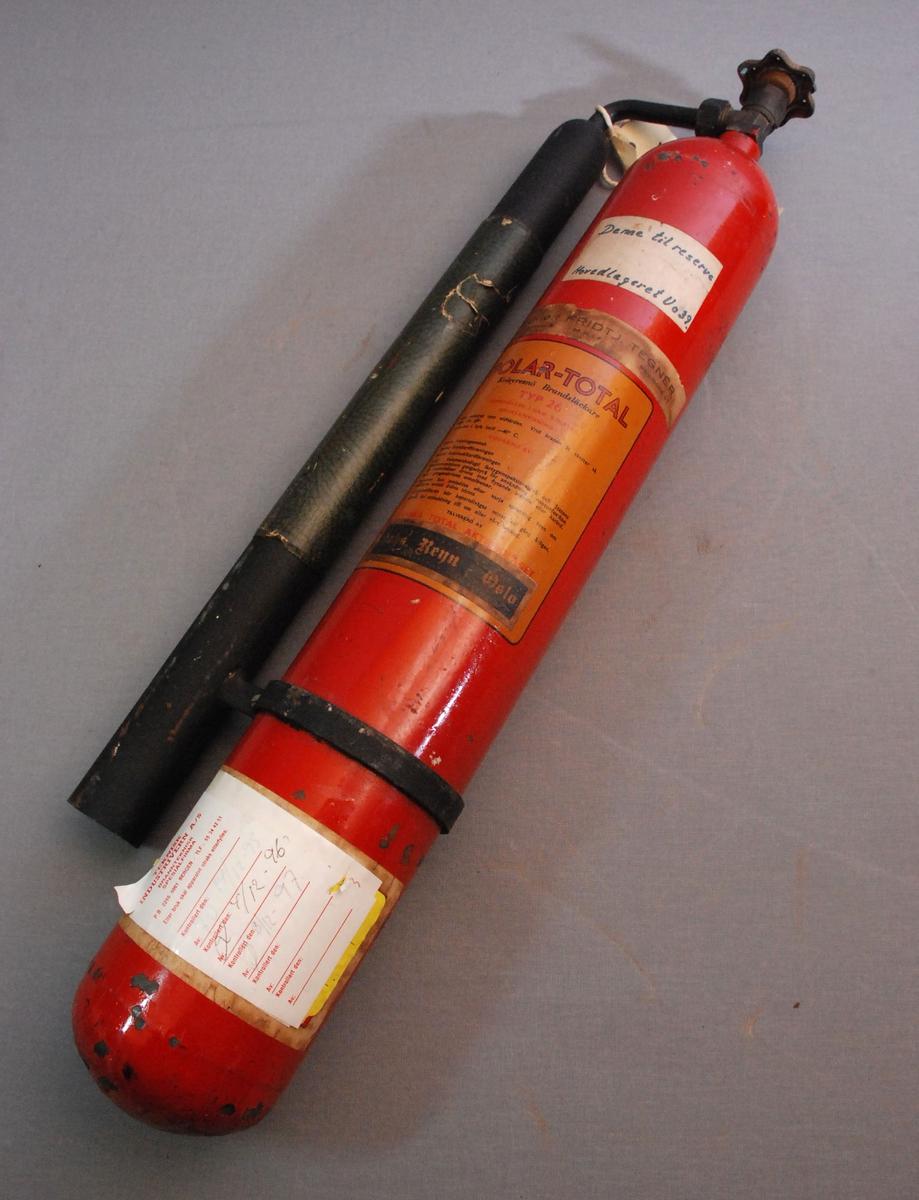 Sylinderformet brannslokkingsapparat med ventilratt på toppen. Et metallbånd rundt korpus med anordning for feste av slokkerør som er koplet til ventilen på toppen. apparatet er rundt i bunnen.
