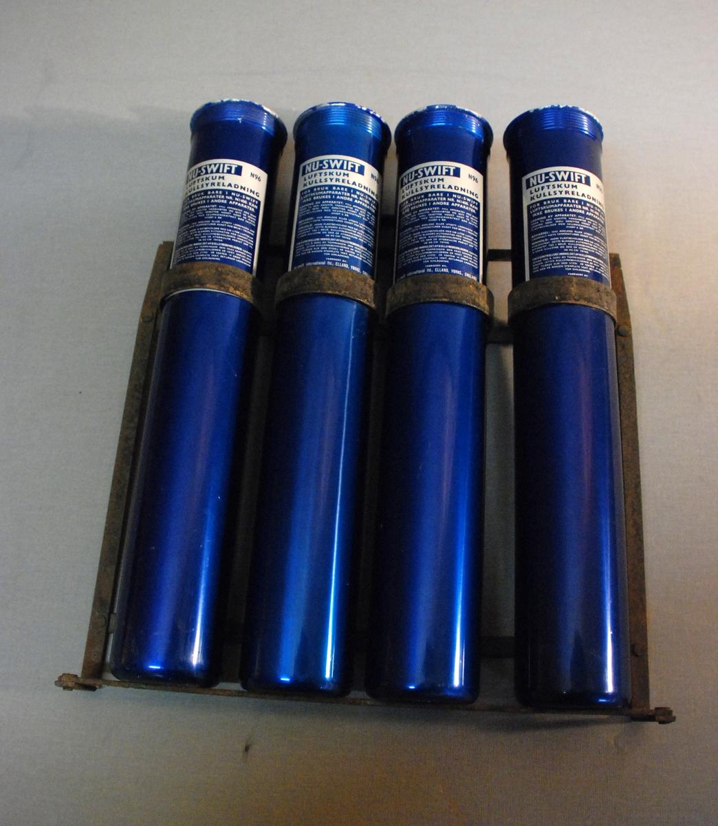 Metallstativ med fire  sylindriske patroner. Blå med hvit påtrykt tekst: Nu-swift Luftskum kullsyreladning M 96