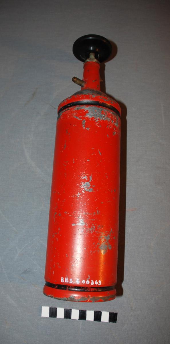 Håndslukker. Sylinderformet med ventil med ratt på toppen. Øverste del av sylinderen er buet og på toppen kjegleformet. Ventilrattet er på toppen av dette