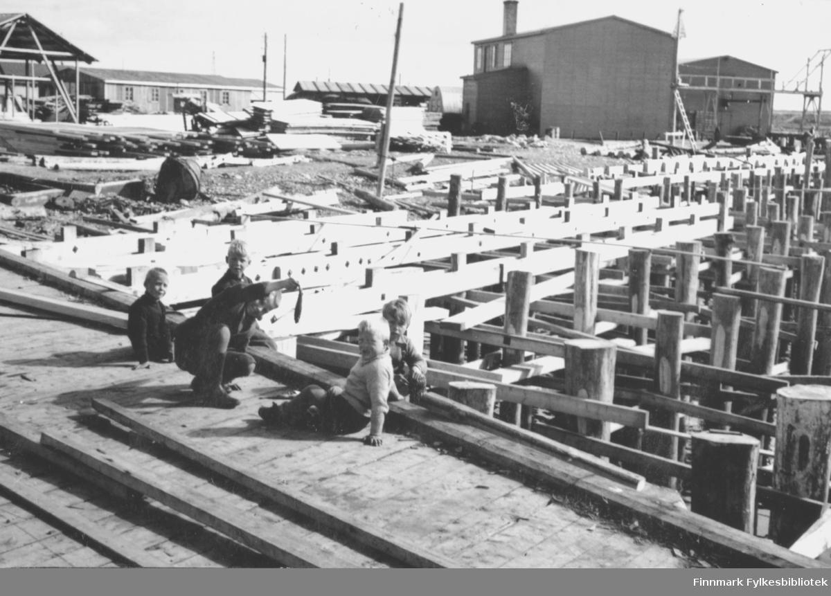 Kaiene bygges opp igjen etter at de ble ødelagt under andre verdenskrig. I forgrunnen sitter fem gutter. Den ene smiler stort og holder opp en fisk. Bak guttene står reisverket til kaiene, og endel materialer ligger til venstre i bildet. Helt i bakgrunnen ligger flere brakker og bygninger.