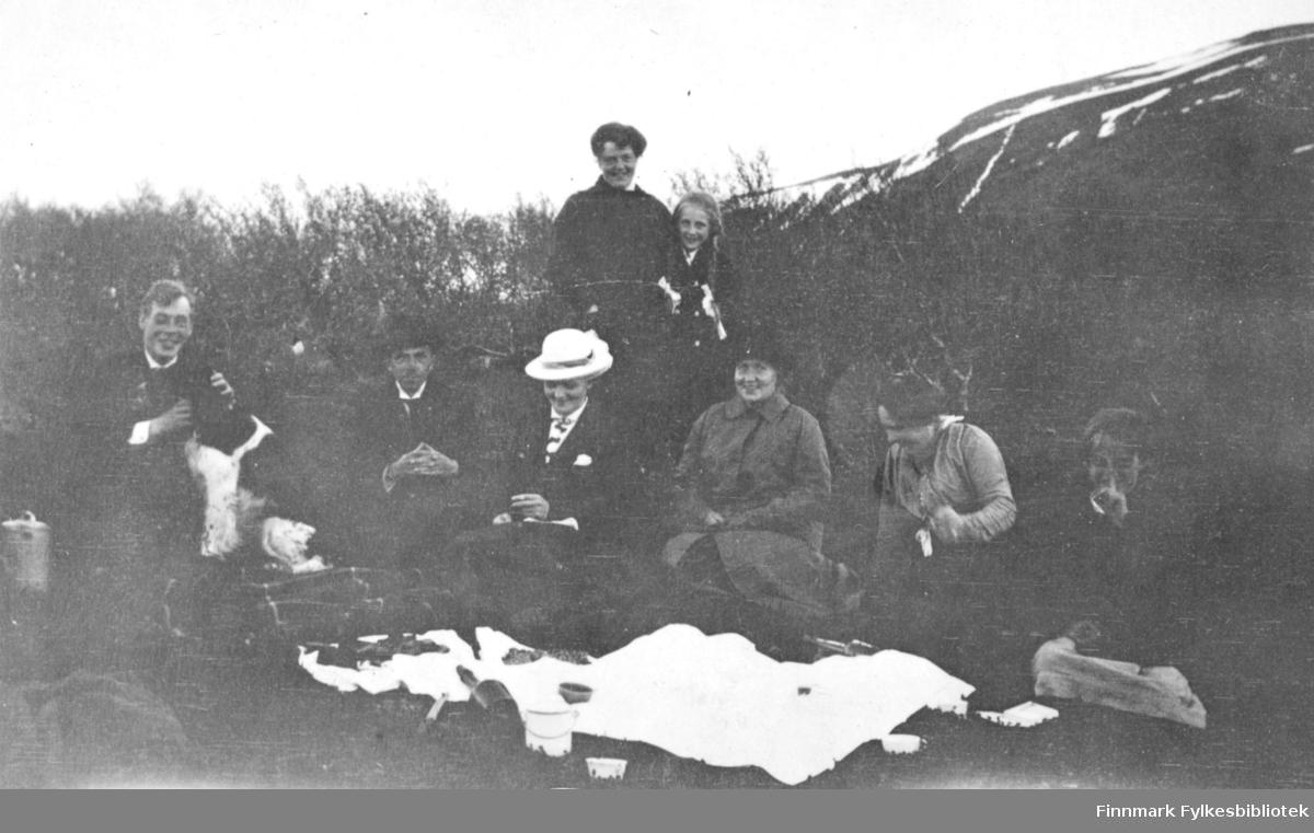St.Hans feiring i Tana. 8 personer og en hund har slått seg ned rundt et pledd for å nyte god mat og drikke. Damen til venstre bak er Signe Solem.
