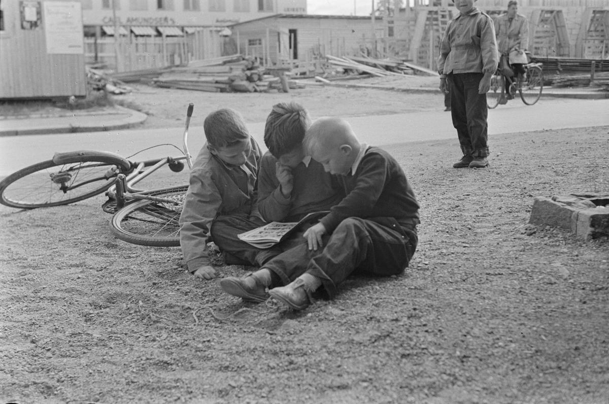 Tre gutter leser tegneserier på fortauet. Leiret, Elverum.